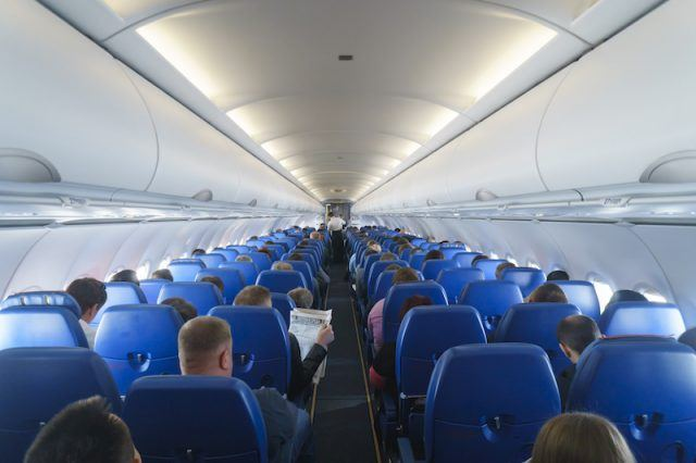 Airline flyers sitting in blue seats.
