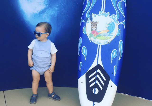 Theodore posing next to a surfboard.
