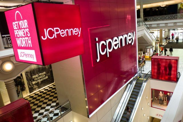 Signage is displayed at the entrance of a JC Penney department store inside the Manhattan Mall,