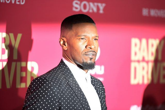 Jamie Foxx posing on a red carpet.