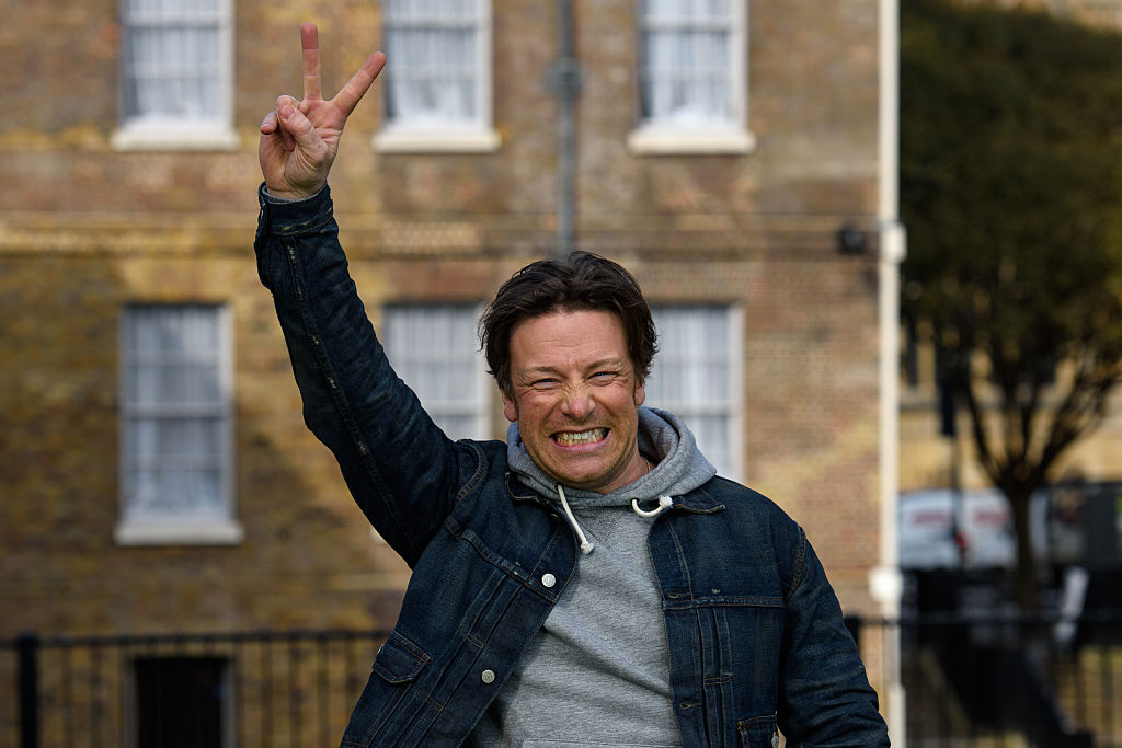 Chef Jamie Oliver smiles and gives a peace sign