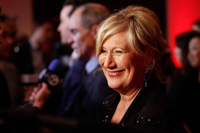 Jayne Atkinson smiling and speaking to the press on a red carpet.