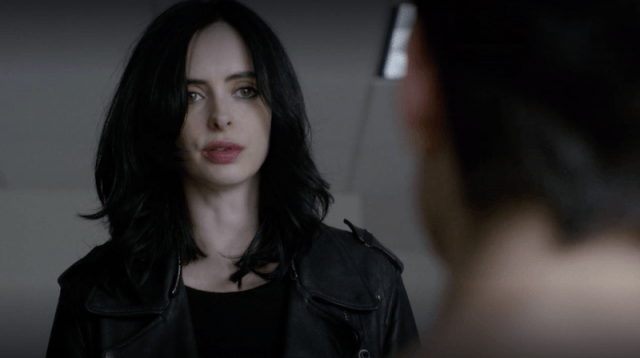 Jessica Jones speaking to a man sitting in front of her.