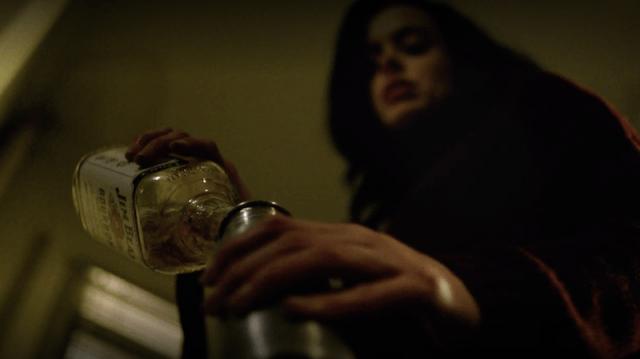 Jessica Jones pouring a drink.