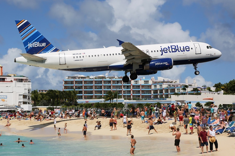 JetBlue plane flying above a beach