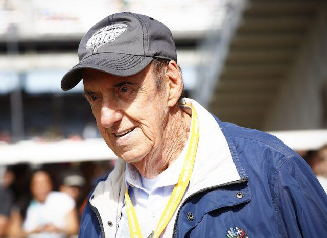 Jim Nabors wearing a jacket and baseball cap.