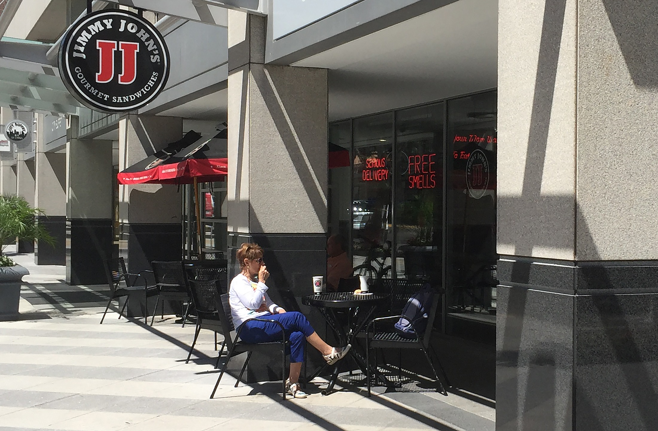 People sit outside one of the shops of Jimmy John's