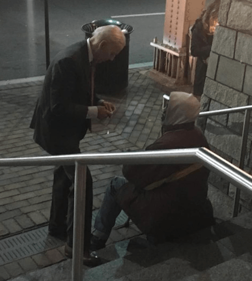 Joe Biden interacting with a man sitting on a staircase.