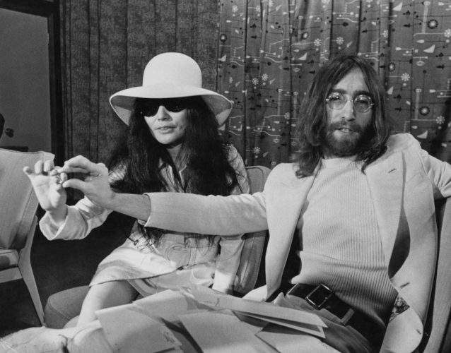 Singer and songwriter John Lennon and his wife Yoko Ono holding acorns during a press conference