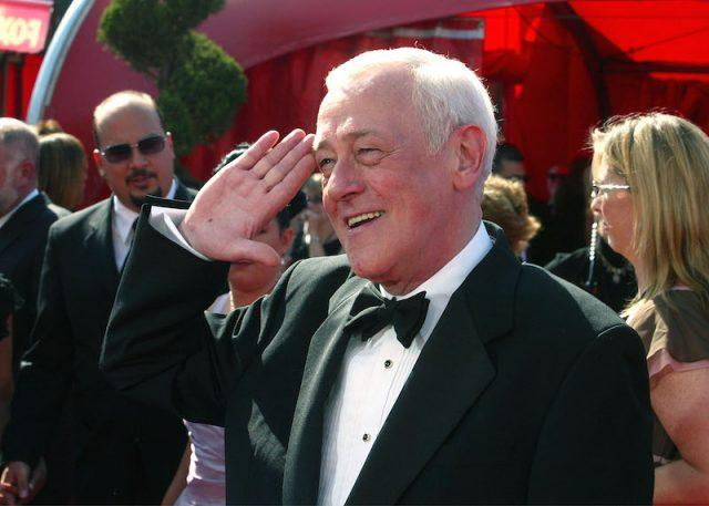 John Mahoney smiling and wearing a black tuxedo on a red carpet.
