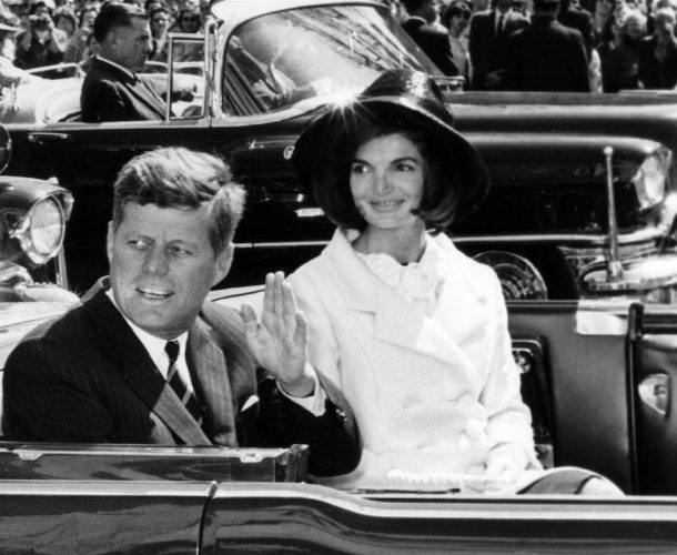 President John F. Kennedy and First Lady Jacqueline Kennedy ride in a parade.