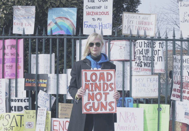 Karlie Kloss holding up a sign at a rally.