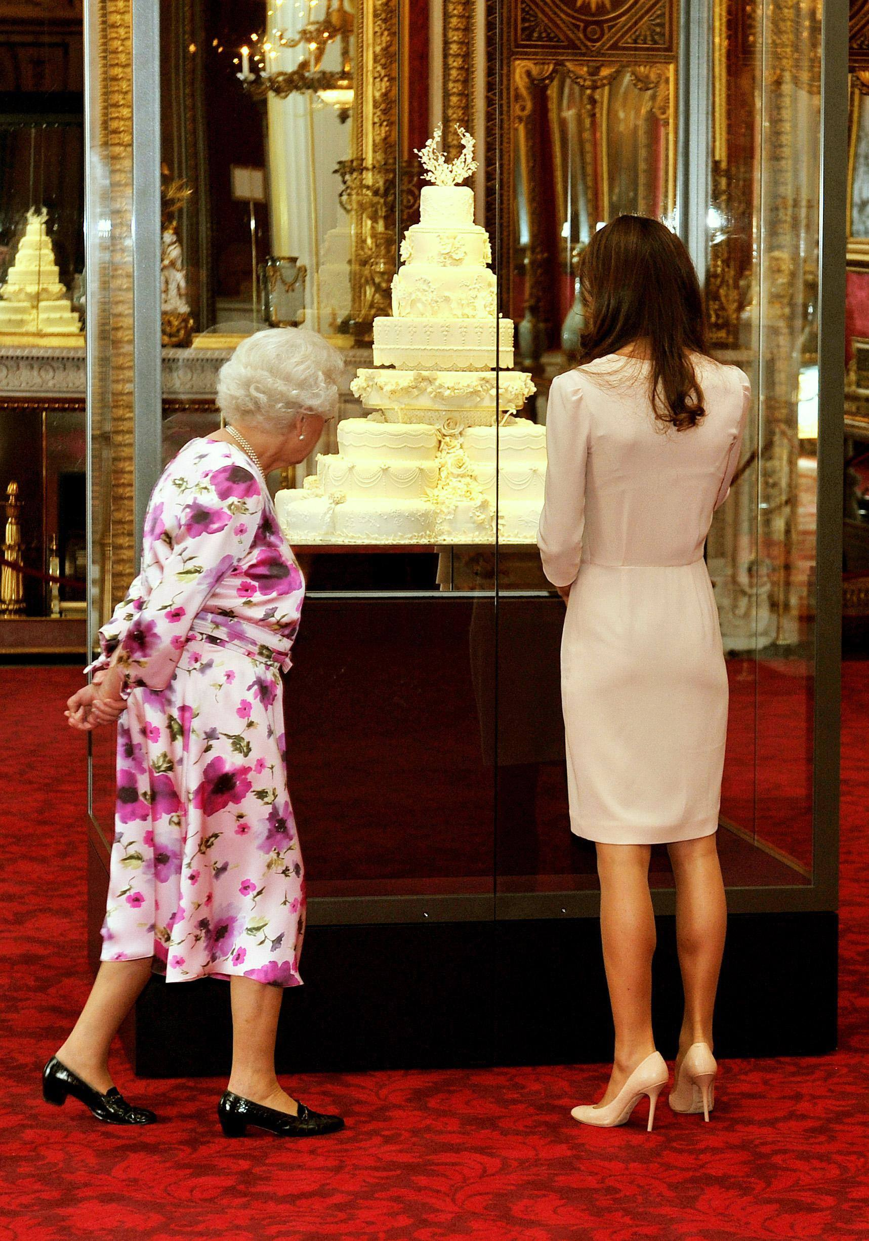 Britain's Queen Elizabeth II (L) and Kate Middleton look at wedding cake in a glass case