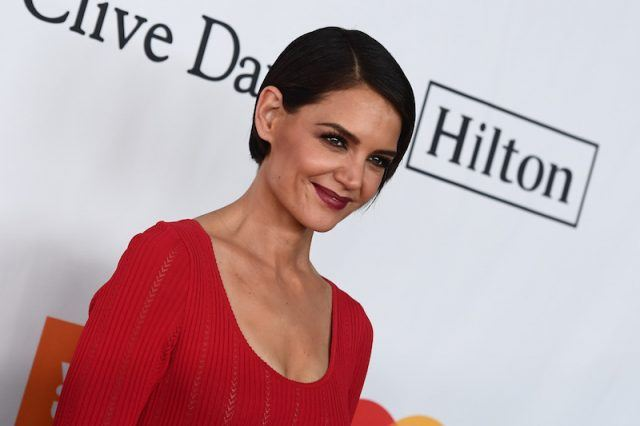 Katie Holmes smiling and posing on a red carpet.