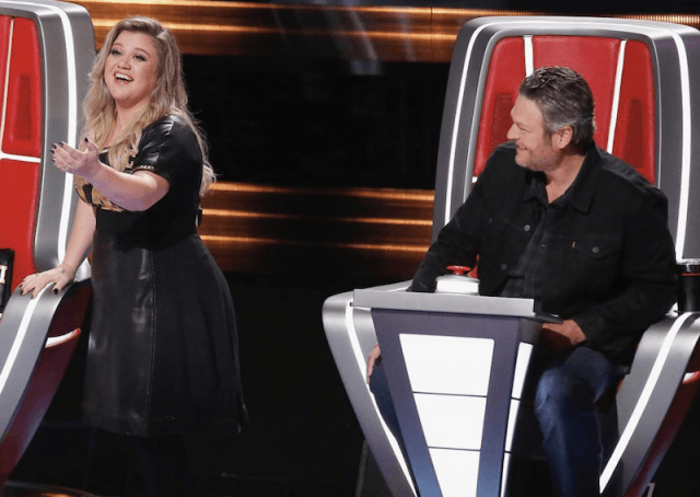 Kelly Clarkson smiling and gesturing towards the stage while next to Blake Shelton.