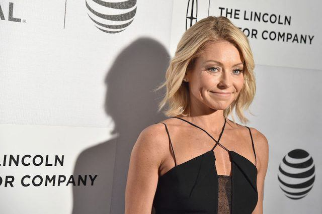 Kelly Ripa posing on a red carpet in a black dress.