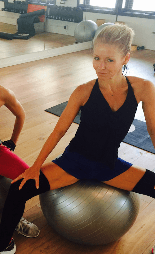 Kelly Ripa posing while excising in a gym studio.