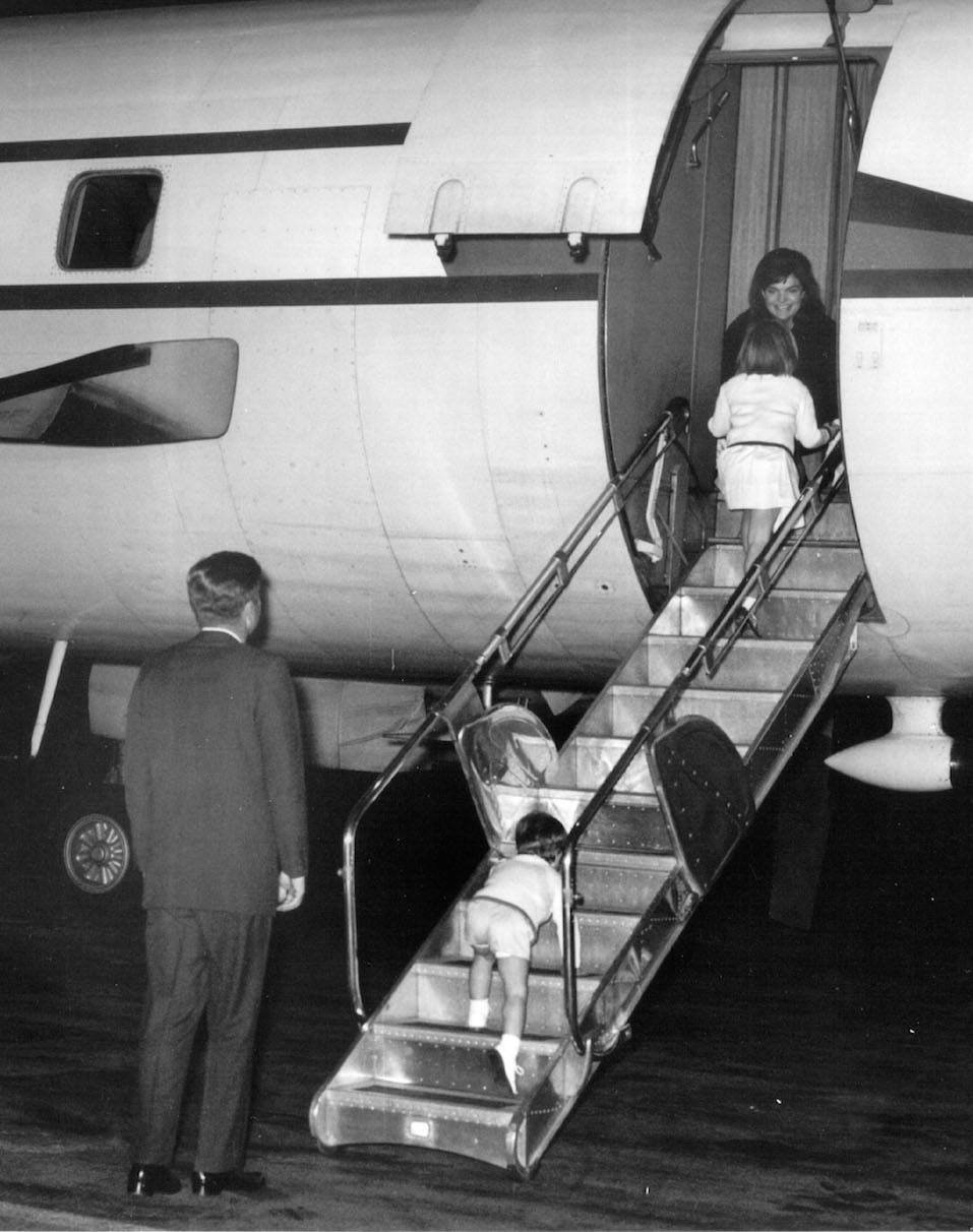 President Kennedy and his children greet First Lady Jackie Kennedy on an airplane