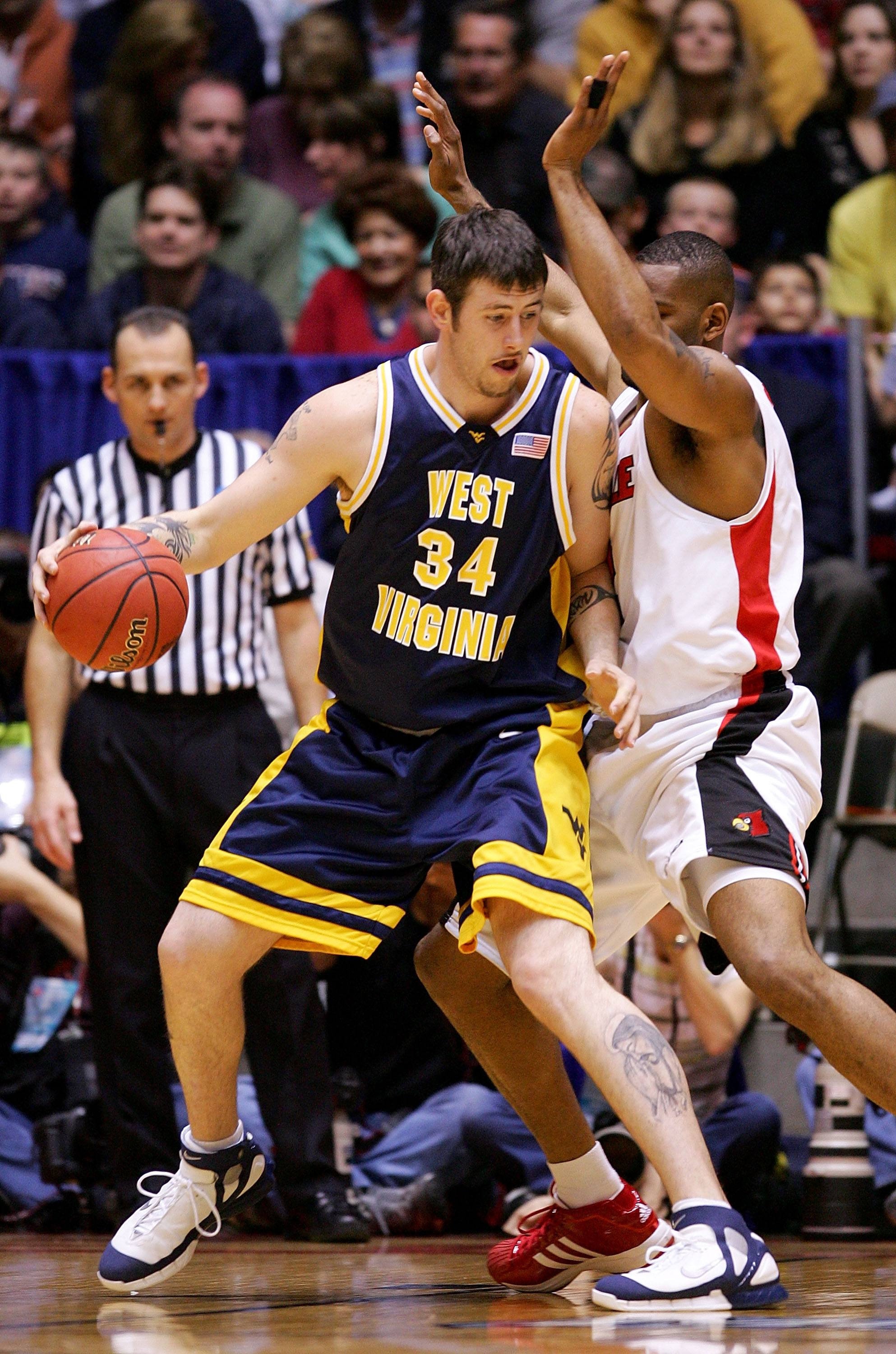 Kevin Pittsnogle #34 of the West Virginia Mountaineers goes up against Ellis Myles #2 of the Louisville Cardinals