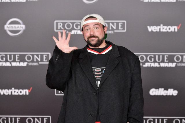 Kevin Smith waving on a red carpet.