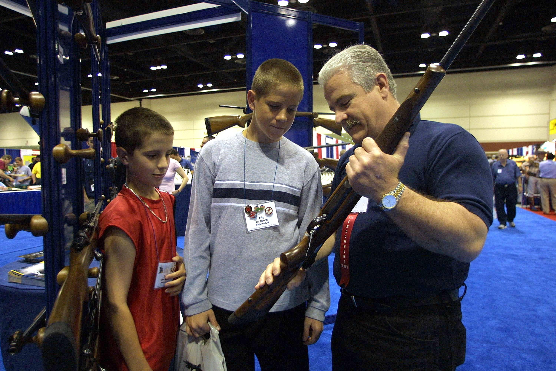 Kids looking at guns at NRA Annual Meeting And Exhibits