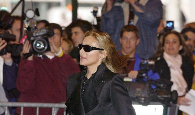 Kim Cattrall walking past a group of photographers while dressed in black clothes.