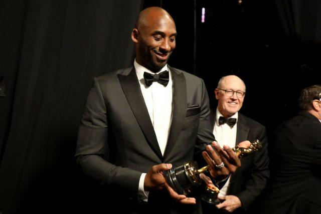 Kobe Bryant smiles while looking down at his Oscar award.