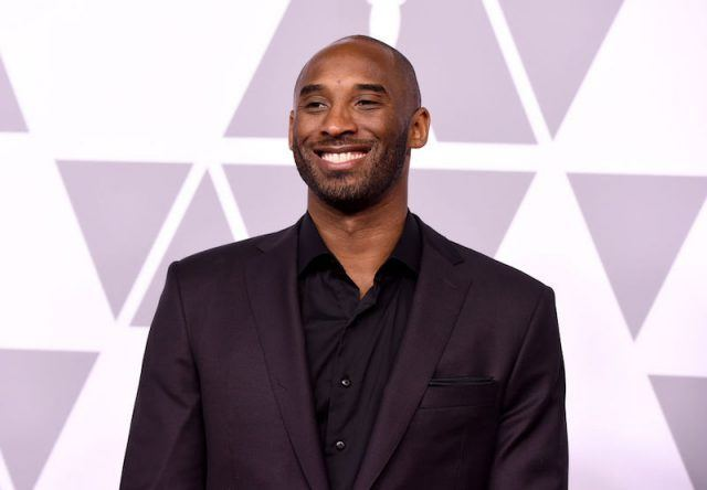 Kobe Bryant smiling while in a black suit.