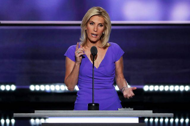 Laura Ingraham posing in front of a black microphone at a podium.