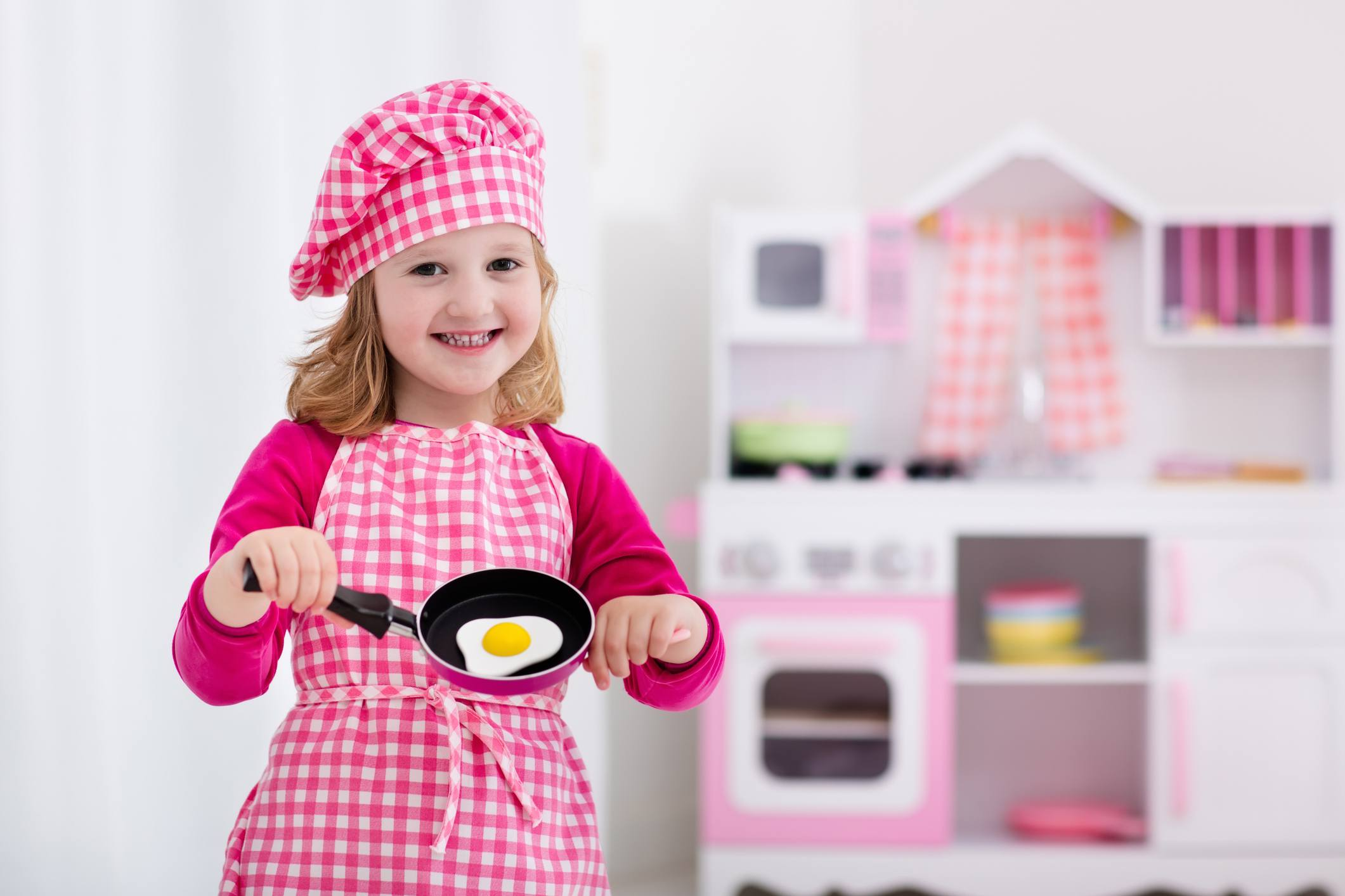 Cute little girl playing with toy kitchen