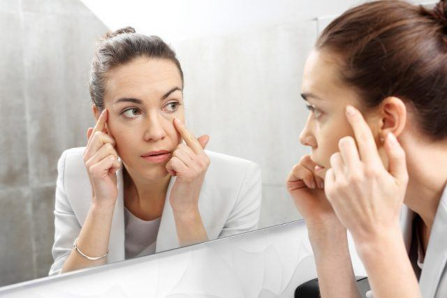 A woman looks into a mirror.