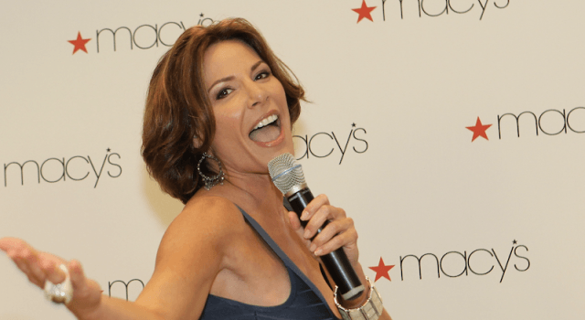 Luann de Lesseps speaking into a microphone at an event.