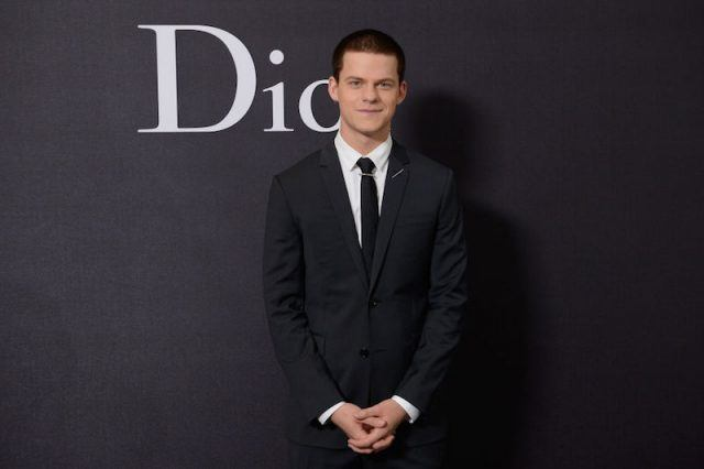 Lucas Hedges posing on a red carpet at a fashion event.