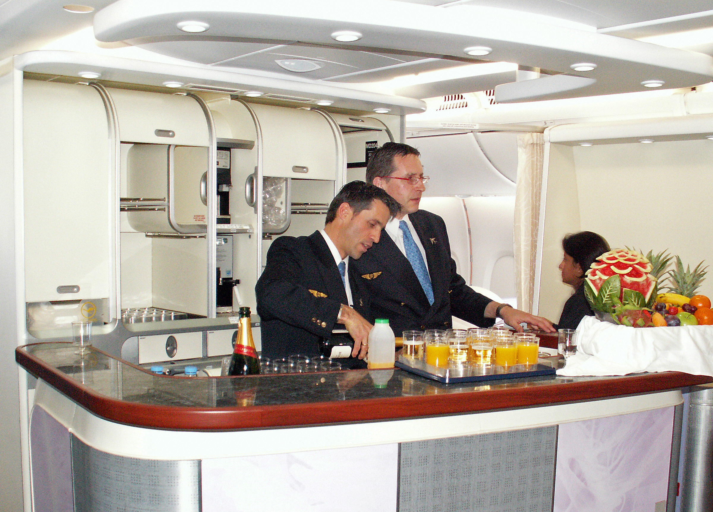 Stewards prepare drinks in the first class bar of Lufthansa aircraft.