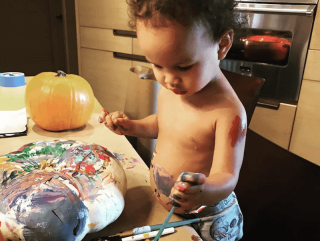 Luna paints a pumpkin with a small paint brush.