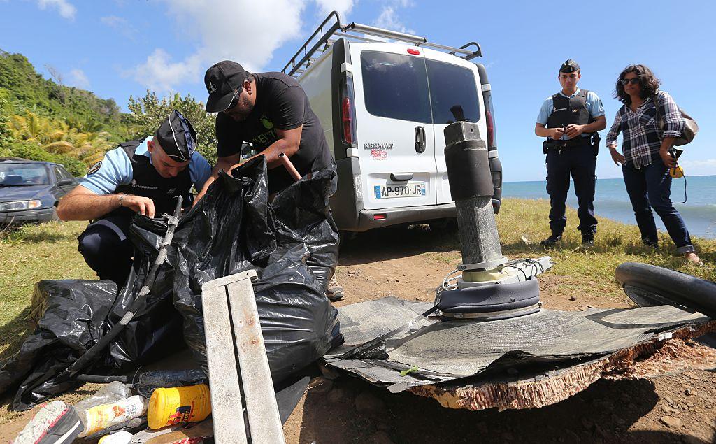 A French Gendarme (L) inspects debris