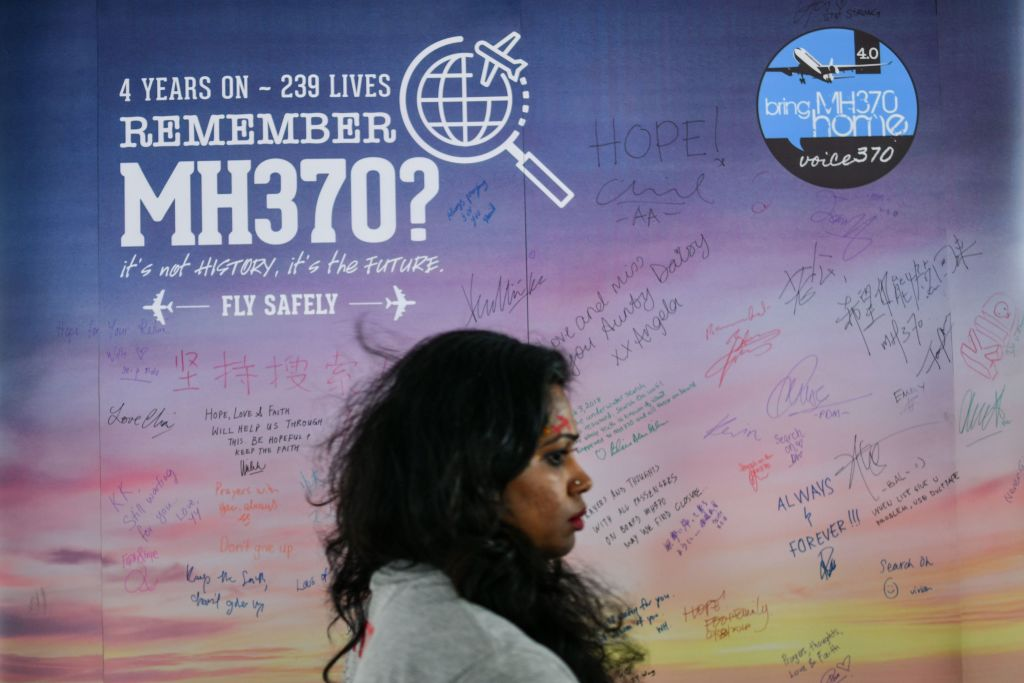 A woman walks past a banner bearing solidarity messages for passengers of the missing Malaysia
