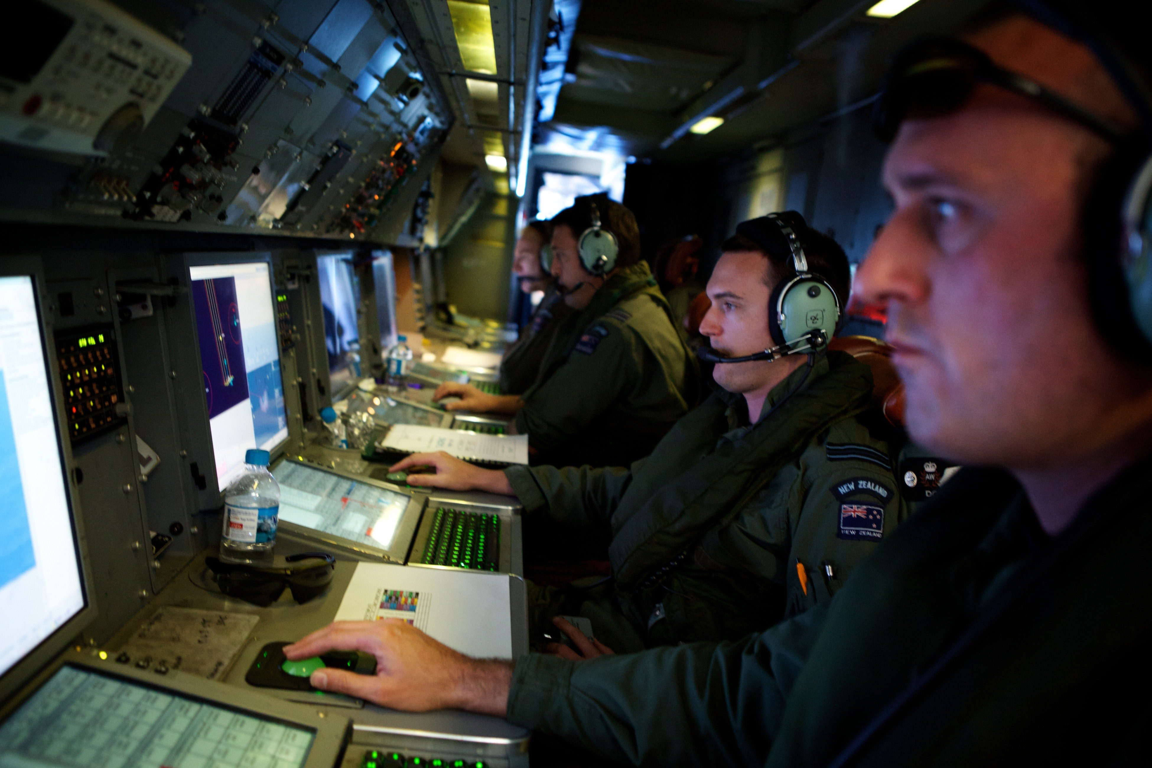 Crew members of a Royal New Zealand Air Force P-3 Orion operate radar