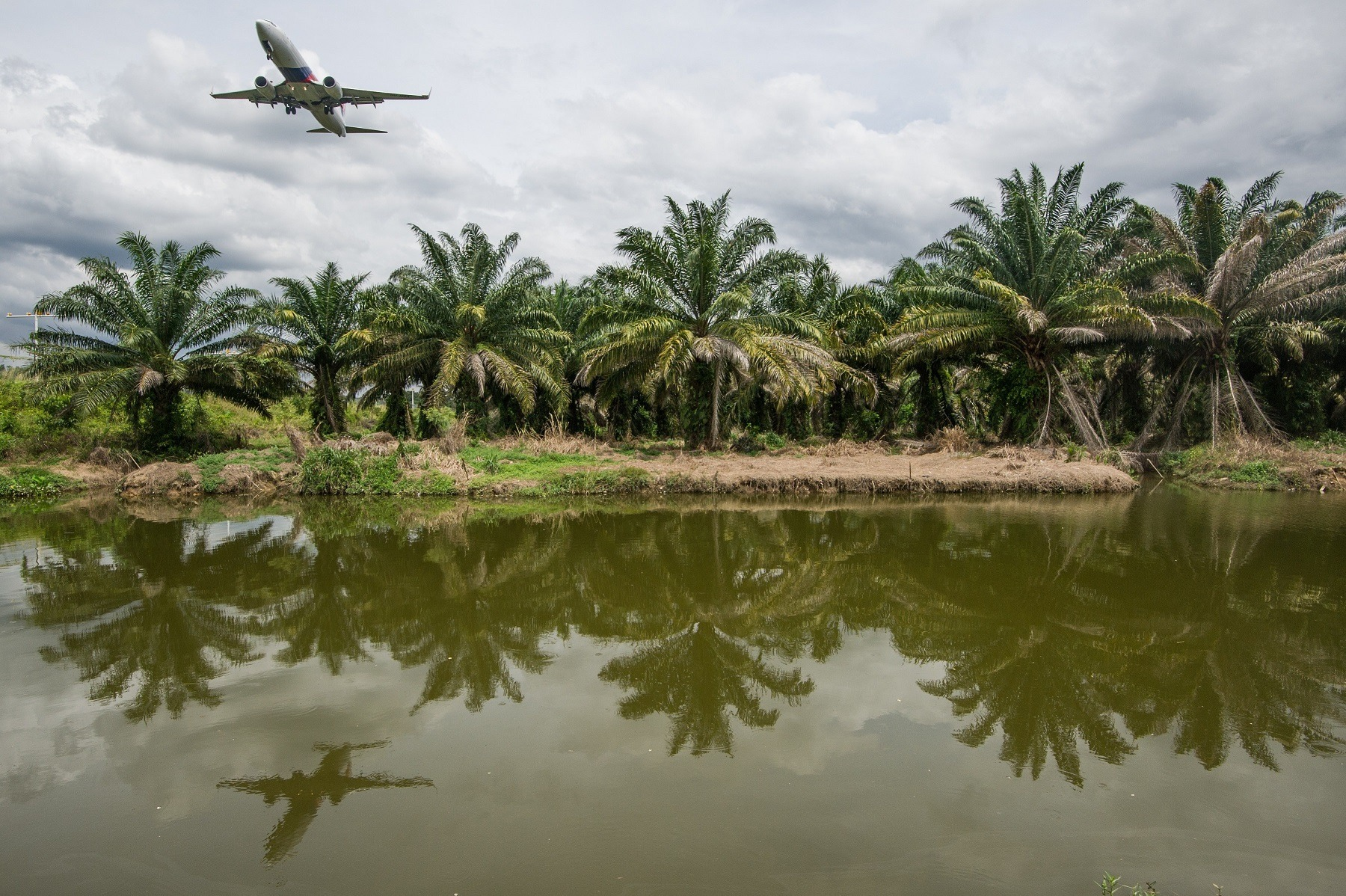 A Malaysia Airlines plane (L) is reflected as it flies over a river