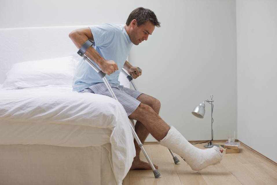 Man with broken leg trying to get up using his crutches