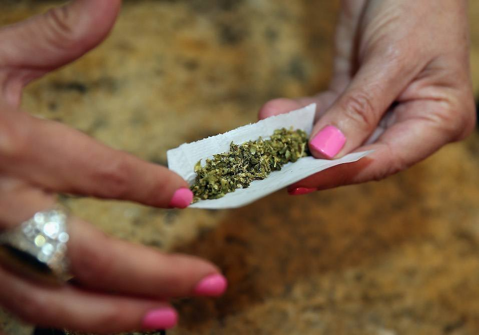 A woman rolls a marijuana cigarette as photographed