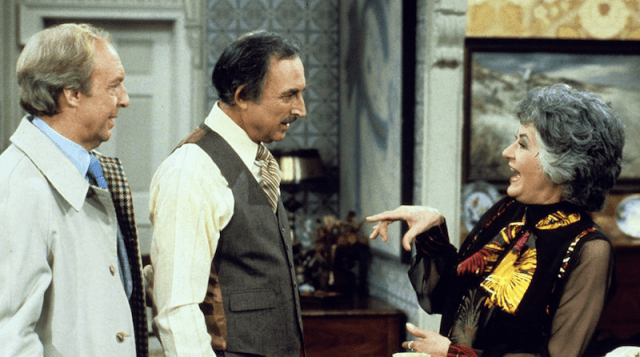 Maude speaking with two men inside an apartment.