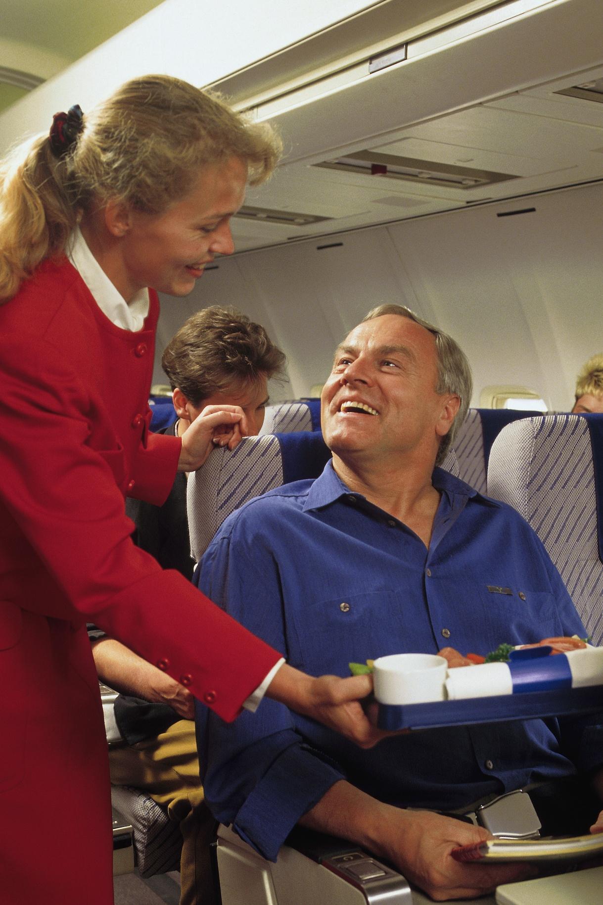 Flight attendant serving passenger on airplane