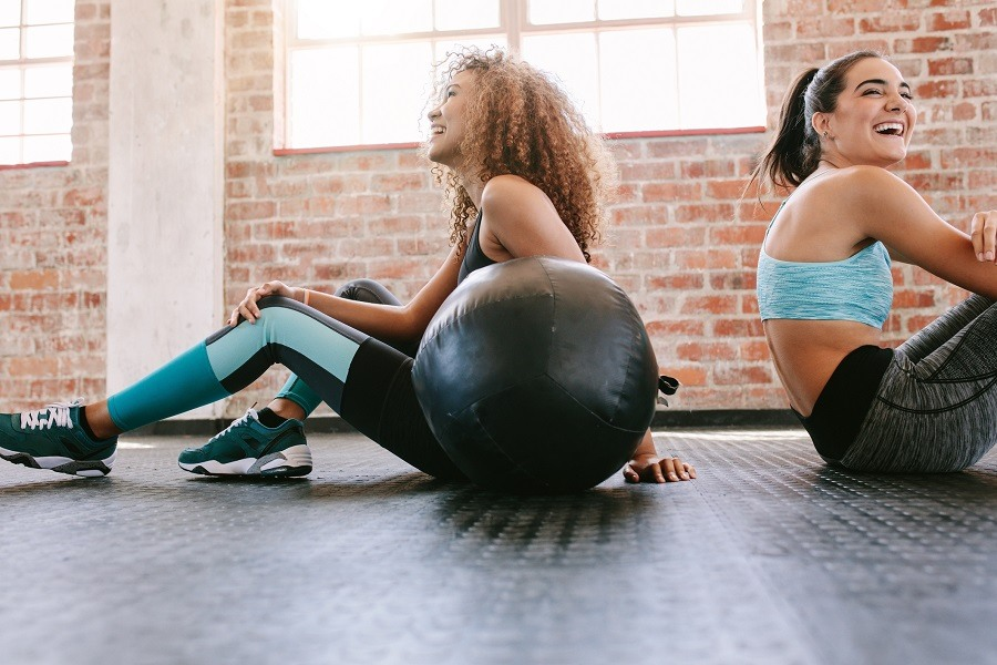 two women working out with a medicine ball
