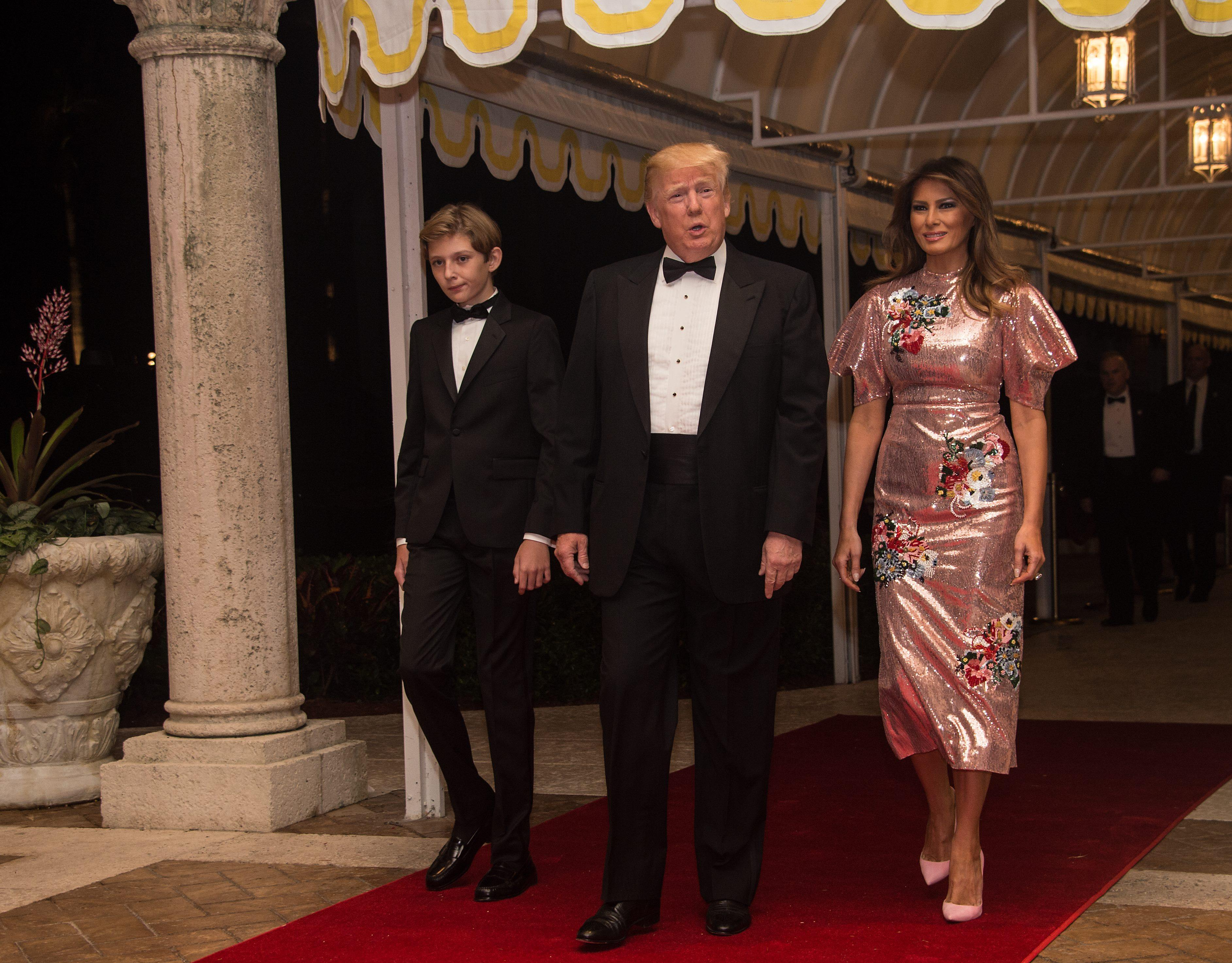 US President Donald Trump, First Lady Melania Trump and their son Barron arrive for a new year's party at Trump's Mar-a-Lago resort