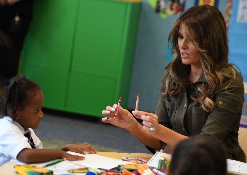 US First Lady Melania Trump hands crayons to a student she visits a youth centre