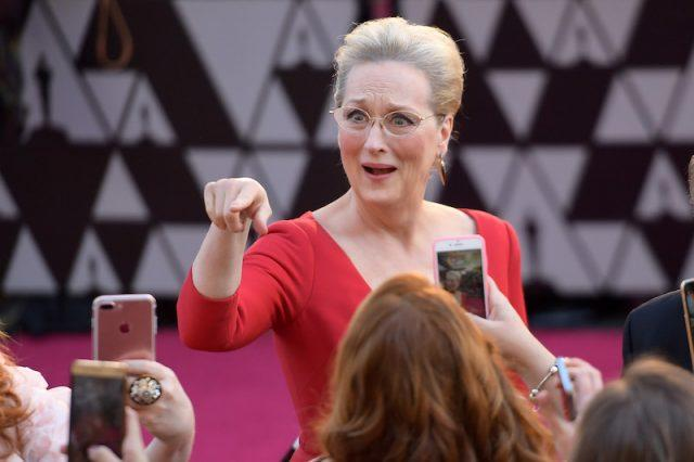 Meryl Streep pointing at someone on a red carpet.