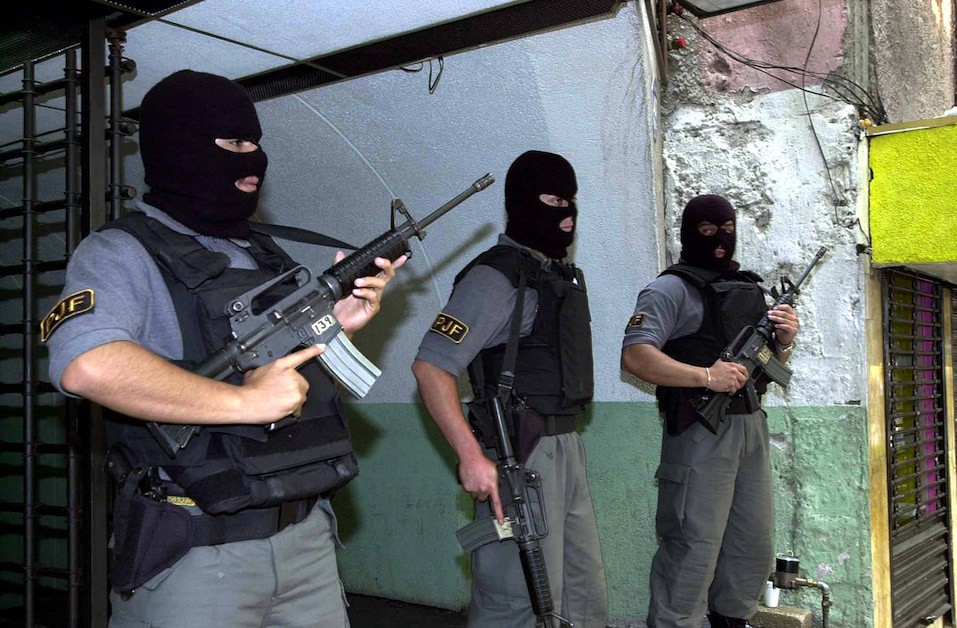 Masked Mexican police stand guard during a raid of a currency exchange store