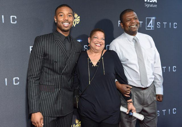 Michael B. Jordan smiling on a red carpet with his parents.