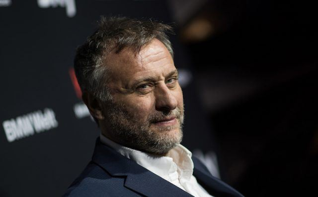 Michael Nyqvist posing on a red carpet.